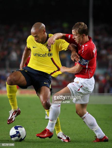 Thierry Henry of Barcelona duels for the ball with Marcin Baszczynski of Wisla Krakow during the UEFA Champions League third Qualifying Round first...