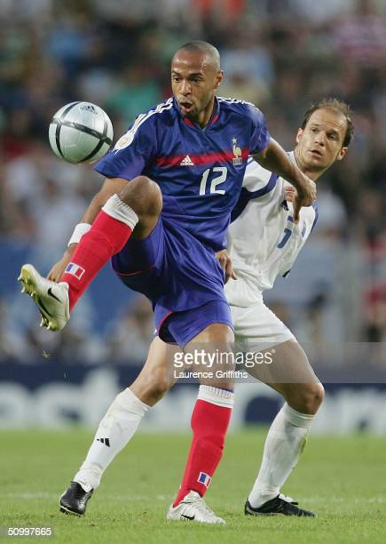 Thierry Henry of France clashes with Angelis Basinas of Greece during the UEFA Euro 2004 Quarter Final match between France and Greece at the Jose...