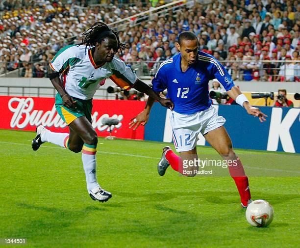 Thierry Henry of France crosses the ball despite the challenge of Ferdinand Coly of Senegal during the second half of the France v Senegal Group A...