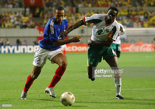 Thierry Henry of France is closed down by Papa Malick Diop of Senegal during the France v Senegal Group A World Cup Group Stage match played at the...