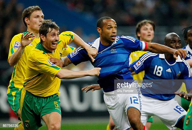 Thierry Henry of France is pulled back by Andrius Skerla of Lithuania during the group 7 FIFA2010 World Cup Qualifier between France and Lithuania at...