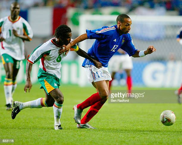 Thierry Henry of France is pursued by Aliou Cisse of Senegal during the second half of the France v Senegal Group A World Cup Group Stage match...
