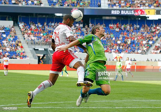 Thierry Henry of the New York Red Bulls heads the ball in the second half against Jeff Parke of the Seattle Sounders at Red Bull Arena on July 15...
