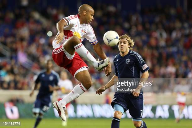 Thierry Henry of the New York Red Bulls takes control of the ball in front of Chance Myers of the Sporting Kansas City at Red Bull Arena on October...