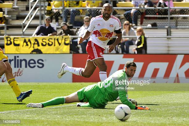Thierry Henry of the New York Red Bulls watches as his touch on the ball goes past goalkeeper Andy Gruenebaum of the Columbus Crew for the third goal...