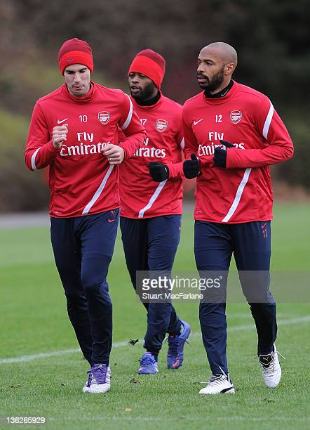 Thierry Henry of the New York Red Bulls with Arsenal captain Robin van Persie during a training session at London Colney on December 30, 2011 in St...