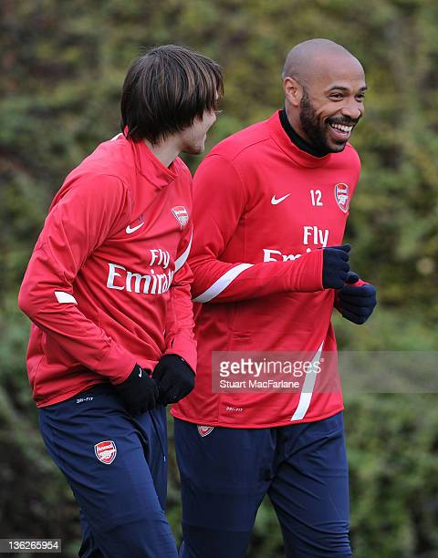 Thierry Henry of the New York Red Bulls with Ignasi Miquel during an Arsenal training session at London Colney on December 30, 2011 in St Albans,...