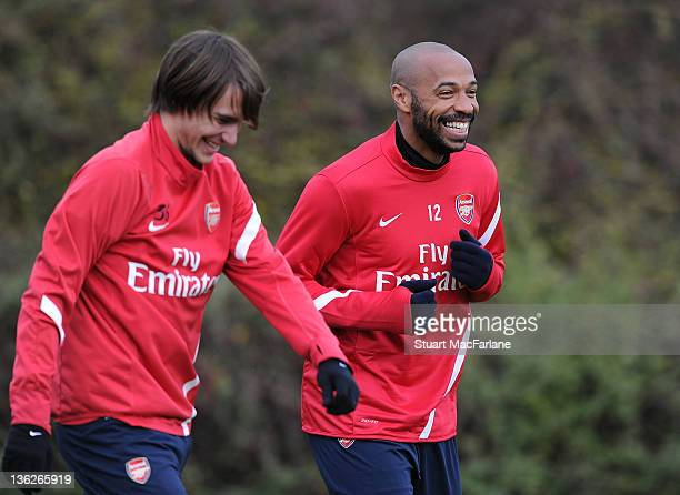 Thierry Henry of the New York Red Bulls with Ignasi Miquel of Arsenal during an Arsenal training session at London Colney on December 30, 2011 in St...