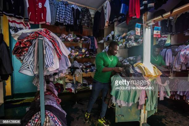 Thierry Ngendahimana who started a secondhand clothes business three years ago arranges stocks at his shop in Kigali Rwanda on June 8 2018 In Rwanda...