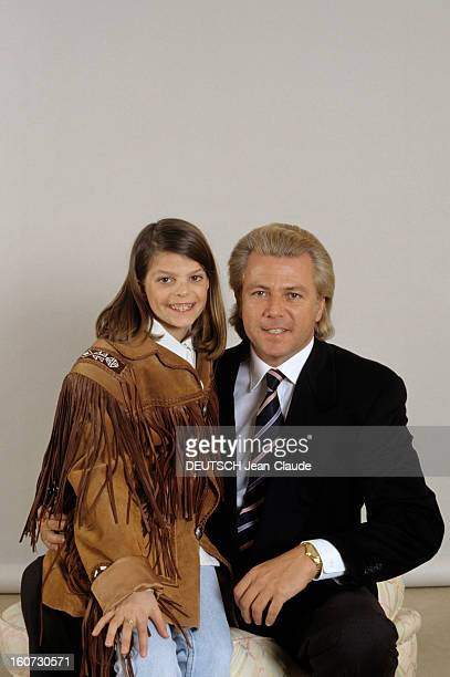 Thierry Roussel And Daughter Athina Pose In Studio Thierry ROUSSEL en costume tenant sur ses genoux sa fille Athina portant une veste western à...