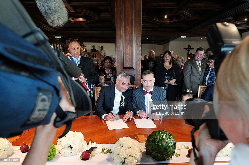 Thierry Speitel (L) and Alexandre Gotz sign during their wedding ceremony at the city hall of Sigolsheim, eastern France, on September 21, 2013. Thierry Speitel, mayor of Sigolsheim, eastern France, who lodged a complaint on May 2 after receiving a letter containing two cartridges, taped to an article of a the Dernieres nouvelles d'Alsace (DNA) newspaper in which he talked about his homosexuality.
