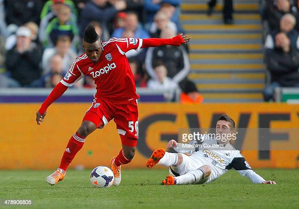 Thievy Bifouma of West Bromwich Albion breaks clear of Pablo Hernandez during the Barclays Premier League match between Swansea City and West...