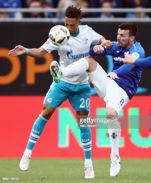 Thilo Kehrer of Schalke is challenged by Jerome Gondorf of Darmstadt during the Bundesliga match between SV Darmstadt 98 and FC Schalke 04 at Stadion...
