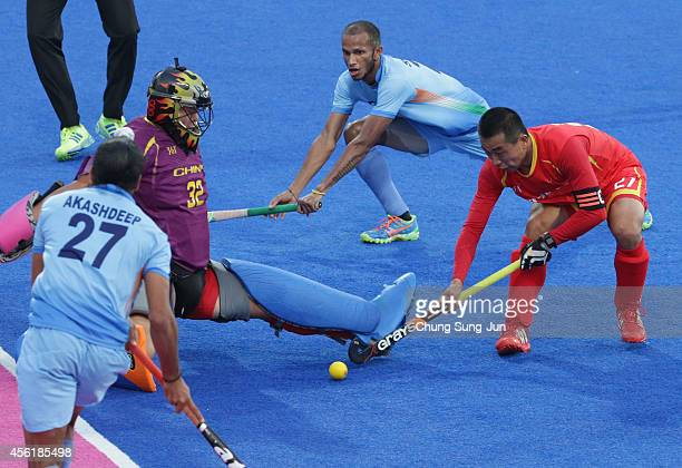 Thimmaiah Chandanda Aiyanna Nikkin of India competes for the ball with Sun Yianjun of China during the Hockey Men's Pool B match between India and...