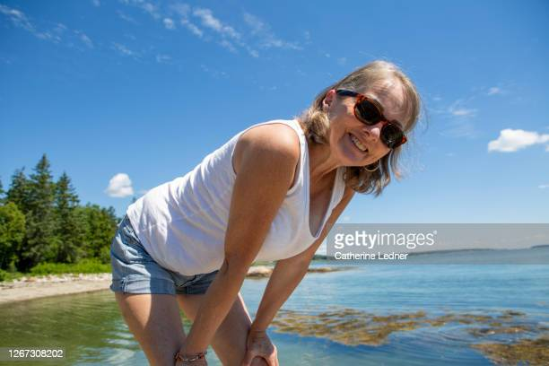 thin 60's woman leaning over while standing on a rock in the ocean looking at camera and smiling - catherine ledner stock pictures, royalty-free photos & images
