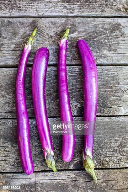 Thin aubergines on wood