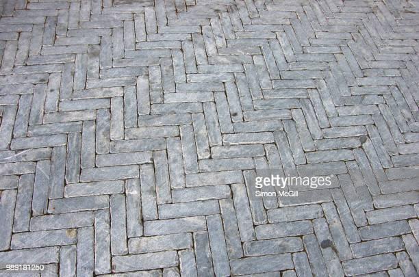 thin grey rectangular paving stones in a herringbone pattern on a pedestrian walkway - herringbone floor stock photos and pictures