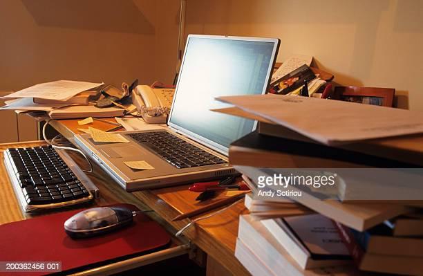 Thin laptop on messy desk