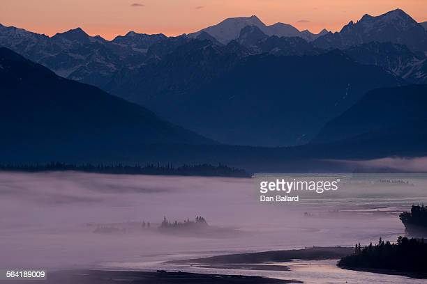 a thin layer of fog blanketed over a river and evergreens with mountains in the background at sunset. denali national park, alaska, usa. - dan peak stock photos and pictures