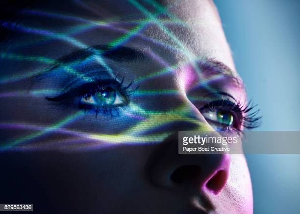 Thin light beams going across the eyes of a woman, shot against a blue studio background