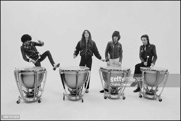 Thin Lizzy pose for a group portrait playing kettle drums on the set of the 'Do Anything You Want To Do' music video London 1979 Left to right Phil...