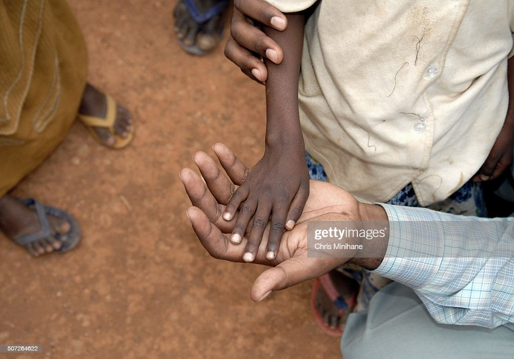 Thin starving child's hand in adult's hand. : Stock Photo