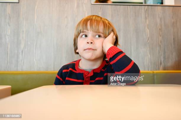 thinking boy (6years) sitting at a restaurant table - 6 7 years stock pictures, royalty-free photos & images