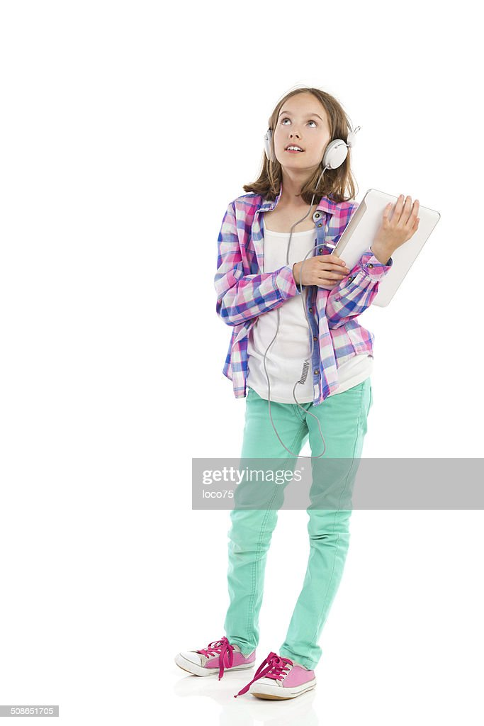 Thinking girl holding a digital tablet : Stock Photo