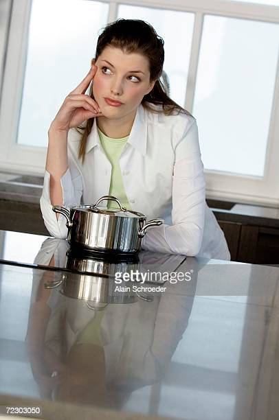 Thinking woman in front of saucepan on vitroceramic hob