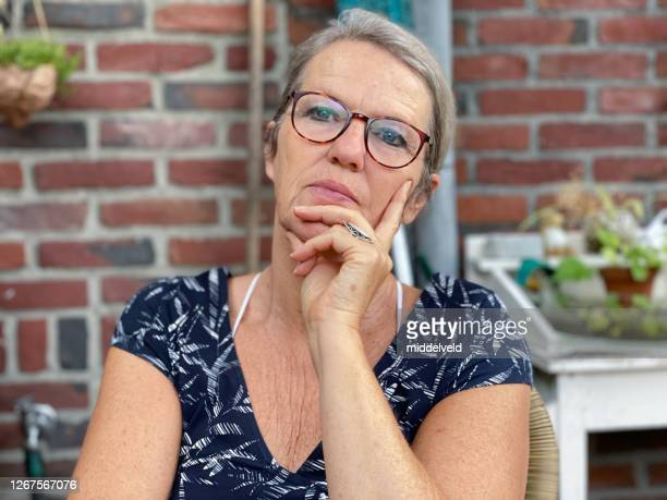 thinking woman with hand on chin - northern european descent stock pictures, royalty-free photos & images