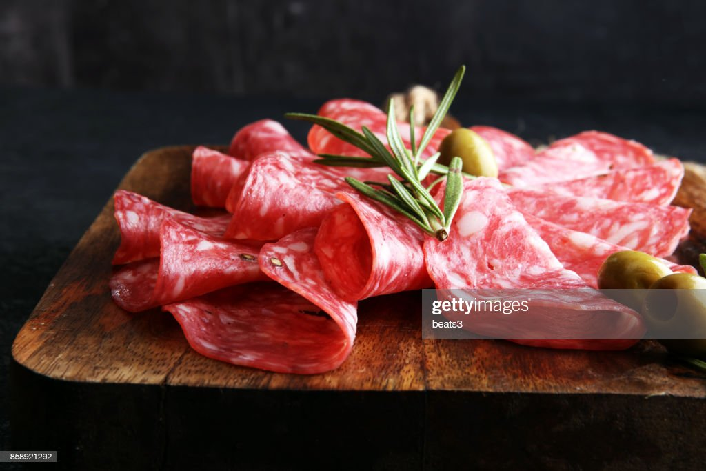 thinly sliced salami on a wooden cuttingboard : Stock Photo