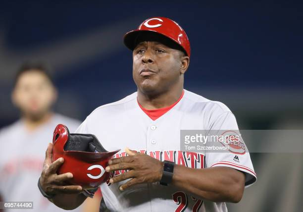 Third base coach Billy Hatcher of the Cincinnati Reds walks off the field carrying a helmet at the end of the first inning during MLB game action...