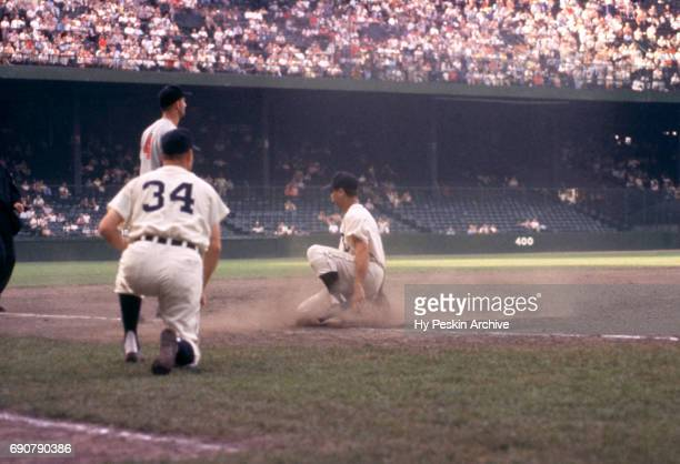 Third base coach Billy Hitchcock of the Detroit Tigers indicates to Charlie Maxwell to slide as thrid baseman George Strickland of the Cleveland...