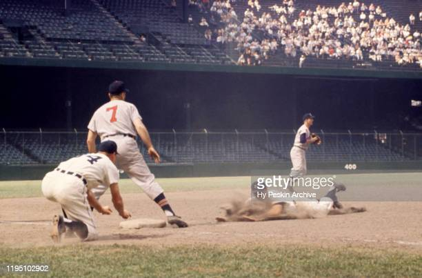 Third base coach Billy Hitchcock of the Detroit Tigers shows Eddie Yost to slide as shortstop George Strickland of the Cleveland Indians throws to...