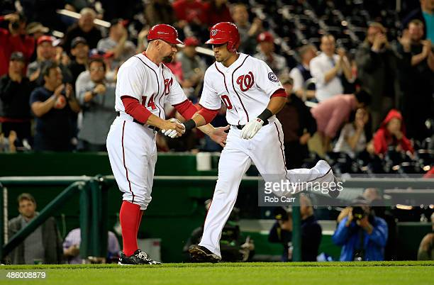 Third base coach Bob Henley of the Washington Nationals congratulates Ian Desmond after hitting a solo home run against the Los Angeles Angels during...