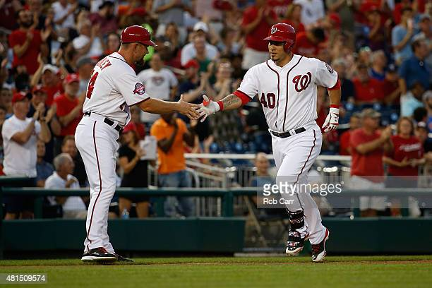 Third base coach Bob Henley shakes hands with Wilson Ramos of the Washington Nationals after Ramos hit a two RBI home run against the New York Mets...