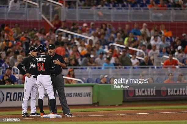 Third base coach Brett Butler and Ichiro Suzuki of the Miami Marlins stand at third base and talk with an umpire after Ichiro was called out at...