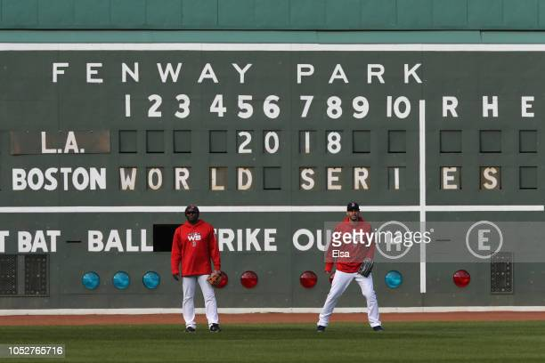 Third base coach Carlos Febles and JD Martinez of the Boston Red Sox look on during team workouts ahead of the 2018 World Series against the Los...