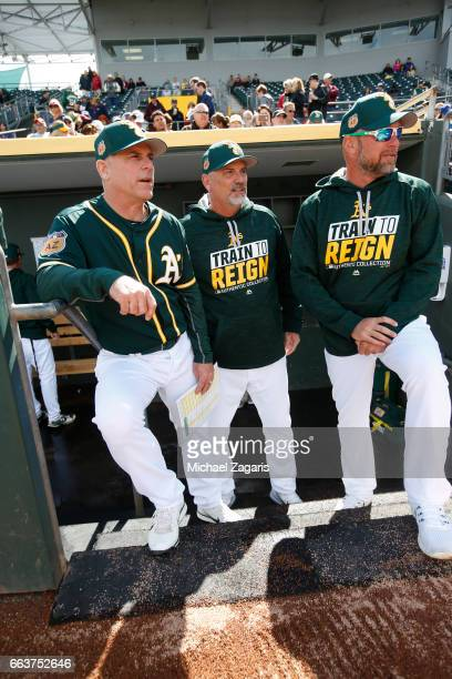 Third Base Coach Chip Hale Coach Steve Scarsone and Bench Coach Mark Kotsay of the Oakland Athletics stand in the dugout during the game against the...