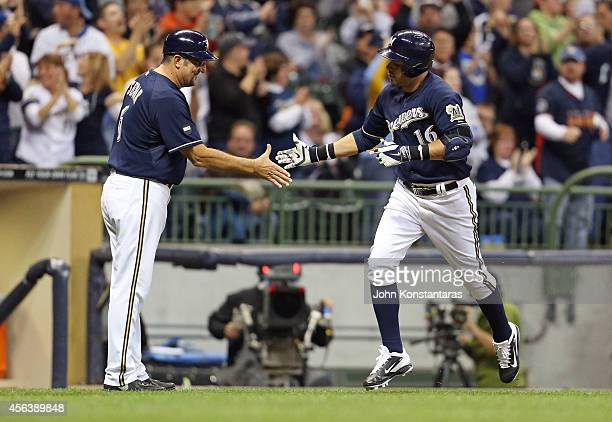 Third base coach Ed Sedar of the Milwaukee Brewers greets Aramis Ramirez of the Milwaukee Brewers after his home run during the fourth inning of...