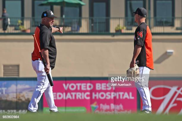 Third base coach Fredi Gonzalez works with Braxton Lee of the Miami Marlins prior to the spring training game against the New York Mets at Roger Dean...