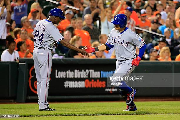 Third base coach Gary Pettis congratulates ShinSoo Choo of the Texas Rangers after hitting a solo home run against the Baltimore Orioles in the fifth...