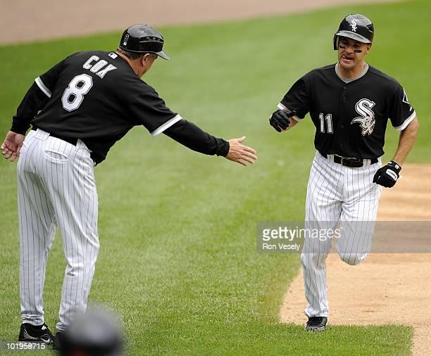 Third base coach Jeff Cox congratulates Omar Vizquel of the Chicago White Sox after Vizquel hit a home run against the Detroit Tigers on June 10 2010...