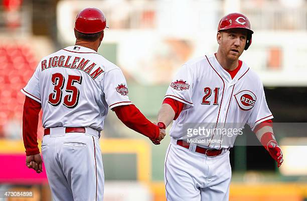 Third base coach Jim Riggleman of the Cincinnati Reds congratulates Todd Frazier of the Cincinnati Reds on a two run home run in the first inning...