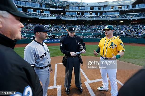 Third Base Coach Joe Espada of the New York Yankees and Stephen Vogt of the Oakland Athletics hand their lineup cards over to umpire Mike Estabrook...
