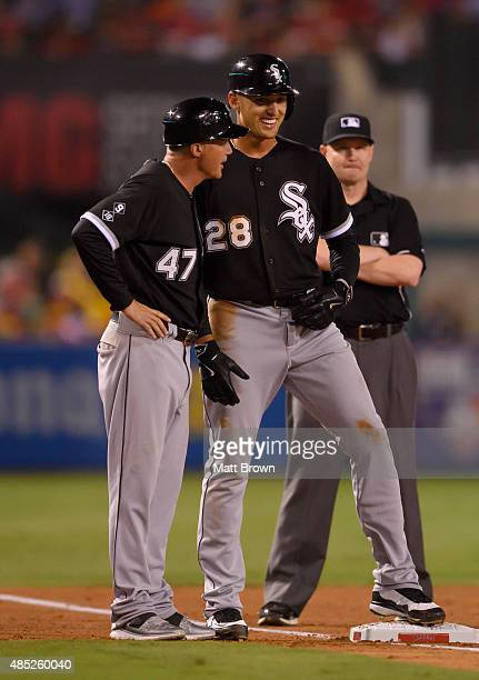 Third base coach Joe McEwing and Trayce Thompson of the Chicago White Sox talk as Thompson smiles during the game against the Los Angeles Angels of...