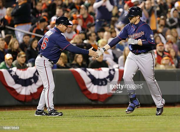 Third base coach Joe Vavra congratulates Chris Parmelee of the Minnesota Twins after hitting a two RBI home run in the third inning against the...
