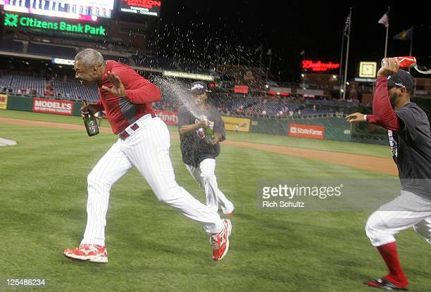 Third base coach Juan Samuel of the Philadelphia Phillies is chased around the infield by Michael Martinez and Antonio Bastardo after defeating the...