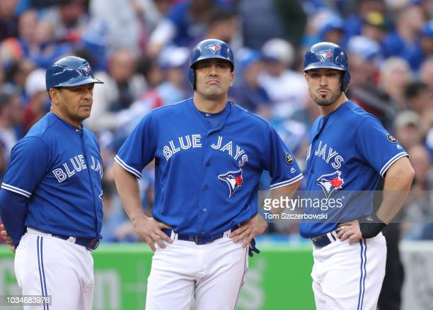 Third base coach Luis Rivera of the Toronto Blue Jays and Kendrys Morales and Randal Grichuk gather at third base during a pitching change in the...