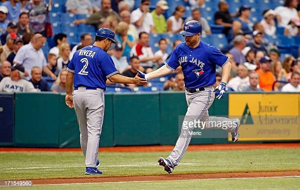 Third base coach Luis Rivera of the Toronto Blue Jays congratulates Adam Lind on his sixth inning solo home run against the Tampa Bay Rays at...